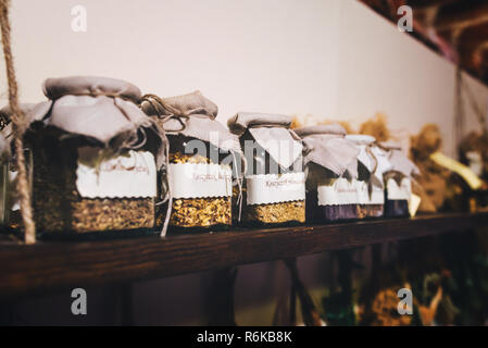 Herbs and spices in glass jars on wooden shelf - Stock Image