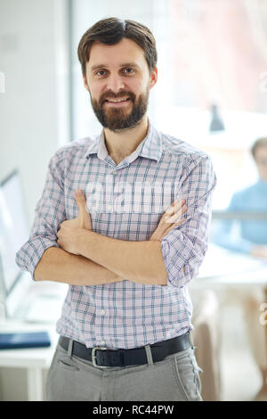Young successful contemporary manager in shirt standing in front of camer swith crossed arms in office - Stock Image