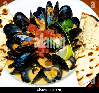 Steamed mussels coconut curry sauce chopped cooked tomato pita bread wedges - Stock Image
