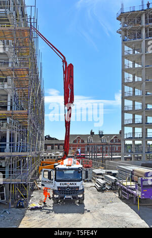 Euromix delivery lorry truck & driver pouring concrete into vertical pumping boom rig to roof level  on confined construction building site London UK - Stock Image