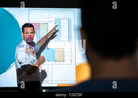 Happy architect during corporate meeting with workers. PR manager talking during presentation for housing project. Business man giving speech to peopl - Stock Image