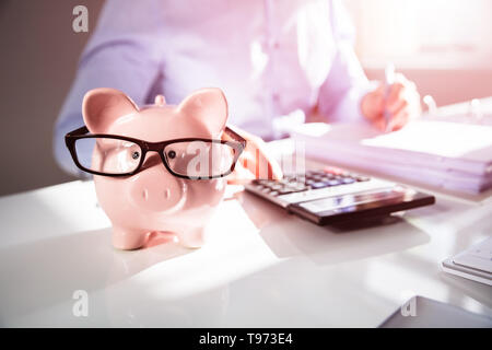 Close-up Of A Businessperson's Hand Calculating Bill With Calculator In Office - Stock Image