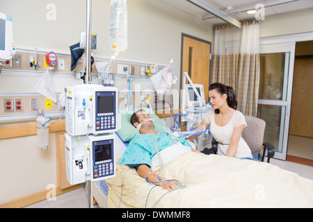 Worried Woman Looking At Critical Patient - Stock Image