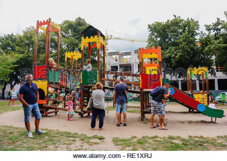 Kolobrzeg, Poland - August 10, 2018: Parents watching their children playing on a equipment with slide at a playground on a cloudy day - Stock Image