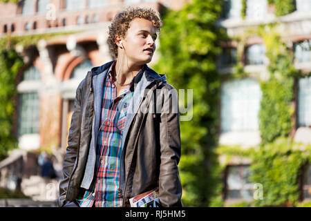 Student in front of a school - Stock Image