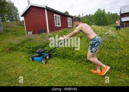 Man mowing the lawn, countryside of northern Sweden. - Stock Image