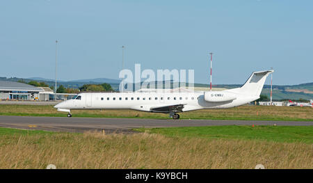 Scheduled Belfast - Inverness Loganair Embraer ERJ-145EU arriving at Inverness Airport.in the Scottish Highlands. - Stock Image