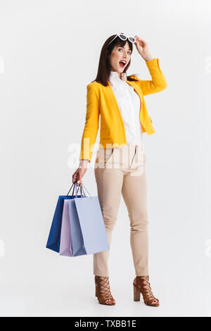 Image of a beautiful shocked young business woman posing isolated over white background holding shopping bags. - Stock Image
