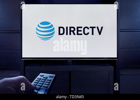 A man points a TV remote at the television which displays the logo for the DirecTV on demand video streaming service (Editorial use only). - Stock Image