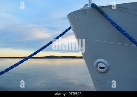 A ship lies moored in an ice covered harbor bay. - Stock Image