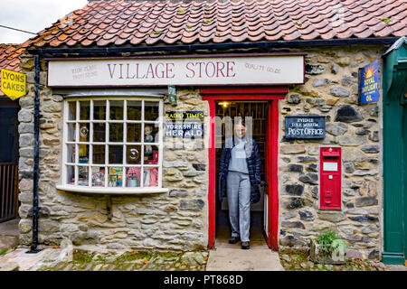 The Village shop and Post Office with a lady visitor at the door at the Ryedale Folk Museum in Hutton le Hole North Yorkshire England UK - Stock Image