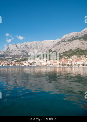 Calm blue sea and city Makarska in Croatia on sunny summer day - Stock Image