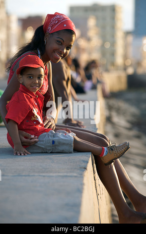 Young Cuban woman with child sitting on the seawall at the Malecon. Havana, Cuba - Stock Image