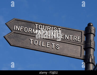 A sign pointing to 'Tourist Information Centre' and 'Toilets', in Ely, UK, against a clear, blue - Stock Image