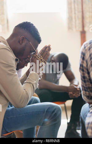 Serene man praying with rosary in prayer group - Stock Image