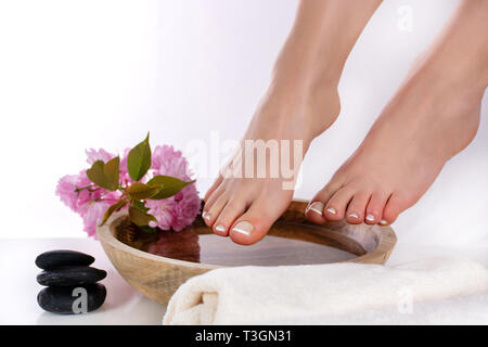 Woman legs and feet with french pedicure on wooden bowl with water and pink flower and decoration black rock and towel in beauty spa salon - Stock Image