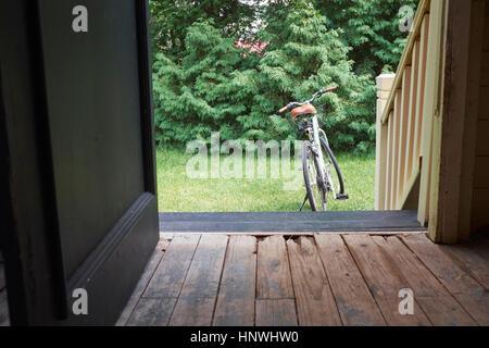 Open front door with bicycle in garden - Stock Image