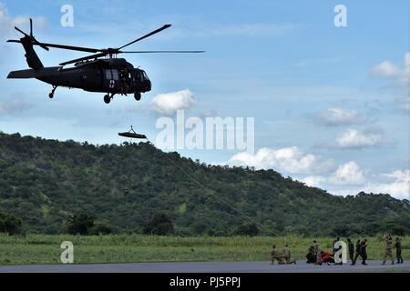 Soldiers from the Washington Army National Guard's Special Operations Detachment – Pacific and rangers from the Royal Thai Army work together to load a Skedco litter into a 16th Combat Aviation Brigade UH-60L Black Hawk during air medical evacuation training Aug. 24 in Thailand's Lopburi province during Hanuman Guardian 2018. The training was part of a four-day tactical combat casualty care class between the Washington Army National Guard's Special Operations Detachment – Pacific Soldiers and Royal Army Thai rangers. More than 500 U.S. Army, Army National Guard and Royal Thai Army Soldiers are - Stock Image