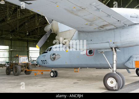 Croatian Air Force An-32B being towed by tractor into hangar - Stock Image