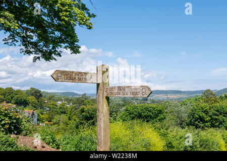Traditional wooden fingerpost signpost on the South West Coast Path, Peak Hill (High Peak), Sidmouth, a south coast seaside town in Devon, SW England - Stock Image