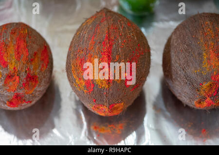 Coconuts decorated with turmeric, sindov And baboot on the alter at a Hindu temple in Queens, New York City. - Stock Image