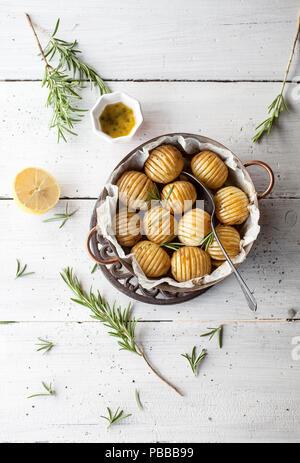 Lemony rosemary potatoes on white table - Stock Image