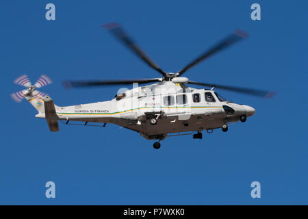 AgustaWestland AW139 helicopter of the Italian Guardia di Finanza or Customs Guard in flight against a clear blue sky - Stock Image