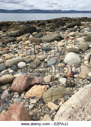 A pebbly beach with the sea in the background - Stock Image