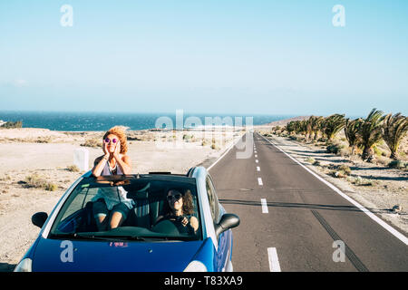 Long way road and friends travel together in freedom and independence concept with couple of young women driving for vacation - happiness and joyful - - Stock Image