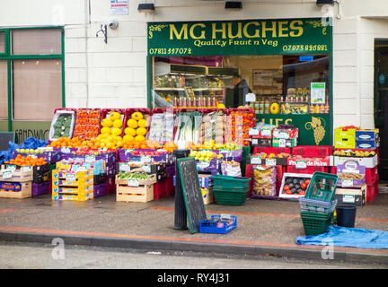 Traditional high street fruit and vegetable greengrocers shop with boxes and crates of fresh produce outside on the pavement in Chirk Wales uk - Stock Image