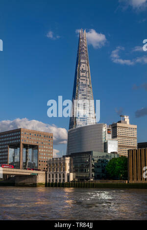 The London Shard with One London Bridge, red bus and riverside city offices. River Thames in foreground viewed from commuter RB1 river boat London UK - Stock Image