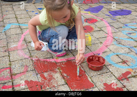 A young girl doing floor paintings - Stock Image