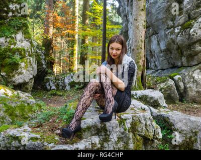 Young beauty female teenager girl in nature sitting on big rock - Stock Image