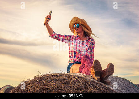 Blonde wearing red checked shirt with sunglasses taking selfi on the top of hale bale - Stock Image