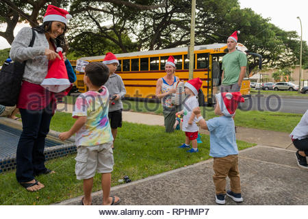Group of young children wearing a Santa hat stocking caps before excursion, Kahala, Honolulu, Oahu, Hawaii, USA - Stock Image