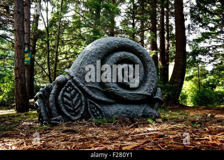 Granite snail sculpture Kitty Coleman Woodland Garden Artisan Festival Courtney BC Canada - Stock Image