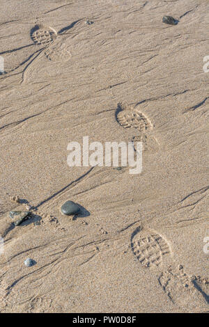 Footprints in the wet sand at Fistral, Cornwall. - Stock Image