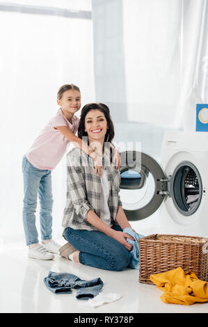 daughter hugging mother near washer and basket in laundry room - Stock Image