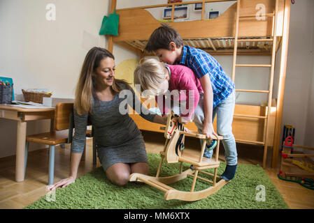 Brothers playing on a rocking horse while pregnant mother is watching them play, Munich, Germany - Stock Image