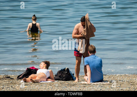 Aberystwyth Wales UK, Wednesday 19 June 2019 UK Weather:After days of unseasonal heavy rain and grey overcast skies, the sun makes a welcome appearance, and draws people back to the beach and the promenade in Aberystwyth on the Cardigan Bay coast, west Wales photo Credit: keith morris/Alamy Live News Credit: keith morris/Alamy Live News - Stock Image