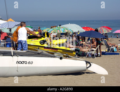 Men Pushing Jet Ski on a trolley across the beach, La Cala de Mijas, Mijas Costa, Costa del Sol, Spain, Europe, - Stock Image