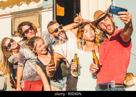 Group of crazy young caucasian people men and women taking selfie pictures doing funny expressions - friendship and youthful concept - old caravan in  - Stock Image