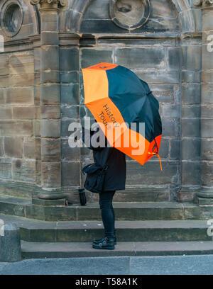 Woman holding large brightly coloured umbrella advertising guided tourist history tour, Mercat Cross, Royal Mile, Edinburgh, Scotland, UK - Stock Image