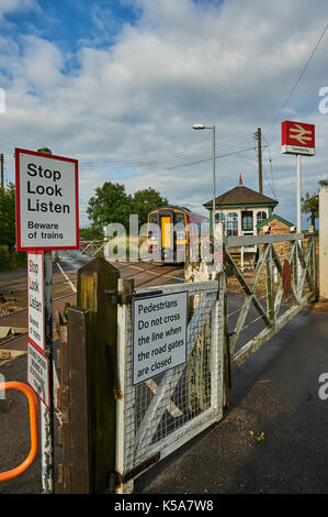 Trains and manually operated level crossing gates at the small Lincolnshire village of Swinderby - Stock Image