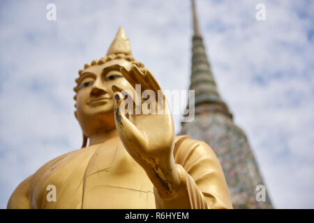 Golden Buddha statue in front of large white pagoda in Wat Arun temple in Bangkok, Thailand, with focus on the hand and out-of-focus background. - Stock Image