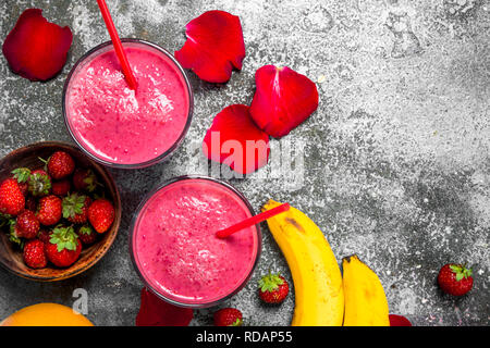 Berry smoothie with banana and rose petals. On rustic background. - Stock Image