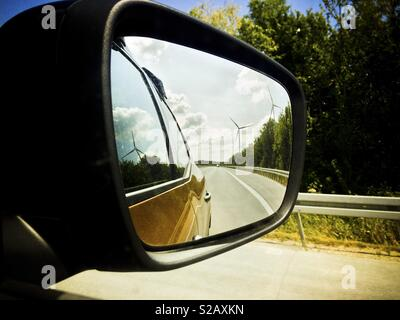 Wind turbine and the road landscape in rear view mirror - Stock Image