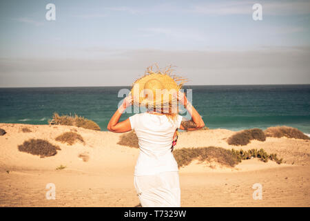 Summer holiday tourist vacation concept with people woman with white dress and hat viewed from back looking wonderful natural outdoor beach and feelin - Stock Image