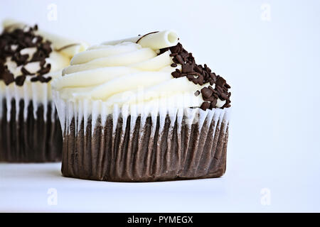 Pretty chocolate flavored cupcake with buttercream icing. Decorated with white chocolate curls and dark chocolate chips. - Stock Image