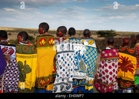 Rear view of Masai Women wearing the traditional shawls called Kangas, in a village near the Masai Mara, East Africa - Stock Image